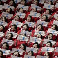 North Korean supporters hold up Korean unification flags during the ladies' 500 meters short-track speedskating event during the 2018 Winter Olympics in Gangneung, South Korea, on Saturday. | AP