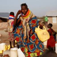 A Turkana woman washes her face at a water point within the Kalobeyei Settlement outside the Kakuma refugee camp in Turkana county, northwest of Nairobi, Thursday. | REUTERS