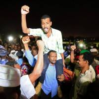 Supporters carry a released politician outside the National Prison, after demonstrations in Khartoum Sunday. | REUTERS