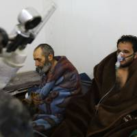 Syrians reportedly suffering from breathing difficulties following Syrian regime airstrikes on the northwestern town of Saraqeb rest around a stove at a field hospital in a village on the outskirts of Saraqeb, due to the lack of hospitals in the town, on Sunday. | AFP-JIJI