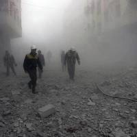This photo provided by the Syrian Civil Defense group known as the White Helmets shows civil defense workers searching for survivors after airstrikes hit a rebel-held suburb near Damascus Monday. | SYRIAN CIVIL DEFENSE WHITE HELMETS / VIA AP