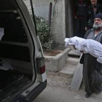 A Syrian man carries the body of a child in the rebel-held besieged town of Arbin, in the eastern Ghouta region on the outskirts of the capital Damascus on Monday following airstrikes. | AFP-JIJI