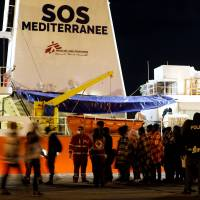 Migrants disembark from the MV Aquarius, a search and rescue ship run in partnership between SOS Mediterranee and Medecins Sans Frontieres, after it arrived in Augusta on Sicily Tuesday. | REUTERS