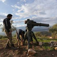 Turkish-backed Free Syrian Army fighters prepare a TOW anti-tank missile north of the city of Afrin, Syria, Sunday. | REUTERS