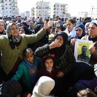 Syrian Kurds mourn in the northern town of Afrin during the funeral on Sunday of fighters from the People's Protection Units (YPG) militia and the Women's Protection Units (YPJ), killed in clashes in the Kurdish enclave in northern Syria on the border with Turkey. | AFP-JIJI