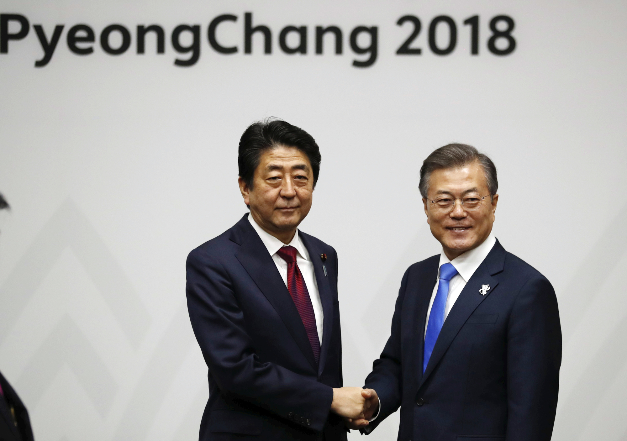 Prime Minister Shinzo Abe shakes hands with South Korean President Moon Jae-in during their meeting in Pyeongchang, South Korea, on Friday.   AP