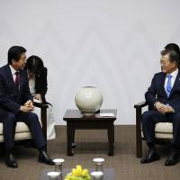 Prime Minister Shinzo Abe meets with South Korean President Moon Jae-in in Pyeongchang, South Korea, on Friday. | AP