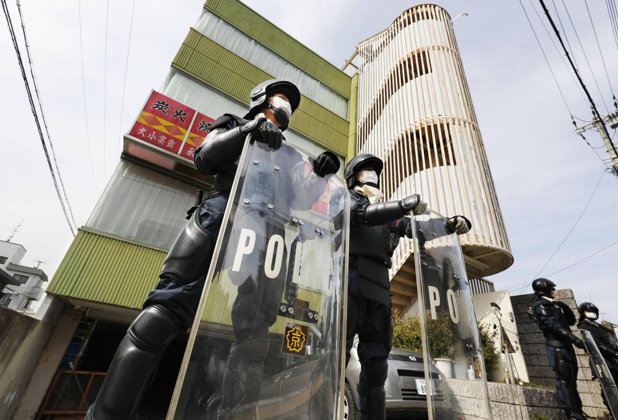 Police officers stand in front of a facility in Kyoto owned by Aleph, an offshoot of the infamous Aum Shinrikyo doomsday cult, on Monday. | KYODO