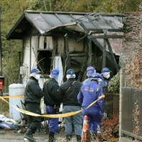 Police officers on Sunday investigate the rubble of a house that burned down the previous day in Inzai, Chiba Prefecture. | KYODO
