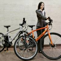 A Panasonic Corp. official shows off sports-type electric bicycles last May in the city of Osaka. | KYODO