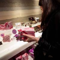 A woman buys sublime ruby KitKats, made of pink ruby chocolate, at a KitKat shop in Tokyo on Feb. 7. | AFP-JIJI