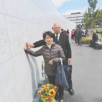 Kikuo and Chizuko Suzuki, whose daughter died in the 2011 Christchurch earthquake, lay flowers at a cenotaph for quake victims in the city on Thursday. | KYODO