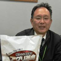 Yutaka Matano of Menicon Co. shows a bag of decomposition accelerant he developed in Nagoya to help Niigata farmers deal with leftover rice straw. | CHUNICHI SHIMBUN