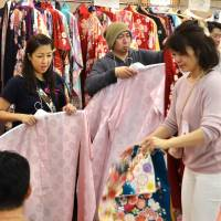 Volunteer workers prepare kimono for new adults in Hachioji, Tokyo, before a Coming-of-Age ceremony held Monday specially for victims of the sudden shutdown of kimono rental firm Harenohi. | KYODO