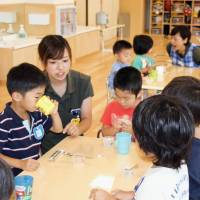 Children eat snacks at a private day care center in Funabashi, Chiba Prefecture, in July 2016. | KYODO