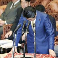 Prime Minister Shinzo Abe apologizes Wednesday at a House of Representatives Budget Committee for a recent remark he made about Japan's discretionary work system reducing working hours. | KYODO