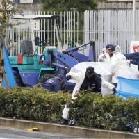 Police inspect the area where a construction vehicle fatally struck students and teachers from a school for children with impaired hearing in Osaka Thursday. The accident killed a student and injured four other people. | KYODO