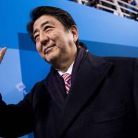 Prime Minister Shinzo Abe waves during the Pyeongchang Winter Olympics in Gangneung, South Korea, on Saturday. Abe said he and South Korean President Moon Jae-in have reaffirmed their shared stance of maximizing pressure on Pyongyang until it scraps its nuclear program. | AFP-JIJI