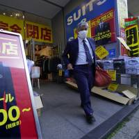 A man leaves a tailor in Tokyo's Nihombashi shopping district on Feb. 19.   AP