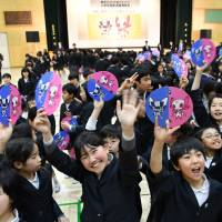Tokyo students react Wednesday to the unveiling of the mascot for the 2020 Olympic Games. | YOSHIAKI MIURA