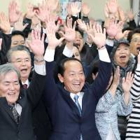 Taketoyo Toguchi (center) celebrates with his supporters Sunday night after winning the Nago mayoral election. | KYODO