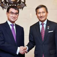 Foreign Minister Taro Kono greets Singaporean counterpart Vivian Balakrishnan on Monday in Singapore. | KYODO