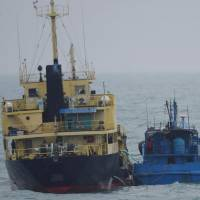 A photo taken by the Japanese Defense Ministry shows what it says is the North Korean-flagged tanker Yu Jong 2 (left) and a smaller vessel with the Chinese characters Min Ning De You 078 in the East China Sea on Friday. | AP