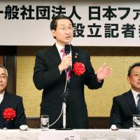 Tottori Gov. Shinji Hirai (center) speaks at a news conference held in Tokyo's Chiyoda Ward Wednesday to announce the establishment of an association to promote minpaku private lodging in rural villages. | KYODO
