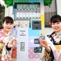 Tourists hold origami bought from a vending machine behind them near Toshogu Shrine, a UNESCO World Heritage site, in Nikko, Tochigi Prefecture, on Feb. 1. | KYODO