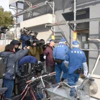 Investigators enter a short-term lodging facility in Osaka's Nishinari Ward on Sunday after a woman's head was found Saturday in a suitcase in one of the rooms.   KYODO