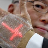 A man holds an ultra-thin elastic display equipped with light-emitting diodes last week developed by professor Takao Someya of the University of Tokyo. | AFP-JIJI