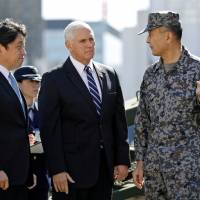 U.S. Vice President Mike Pence speaks with a Ground Self-Defense Force officer as he inspects PAC-3 missile interceptors with Defense Minister Itsunori Onodera at the Defense Ministry in Tokyo on Wednesday.   REUTERS