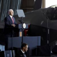 U.S. Vice President Mike Pence addresses members of the U.S. military and the Self-Defense Forces in front of a U.S. Air Force F-35 fighter at the Yokota Air Base on the outskirts of Tokyo on Thursday. | REUTERS
