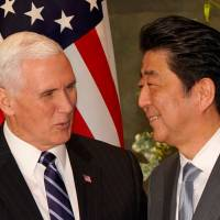 Prime Minister Shinzo Abe greets U.S. Vice President Mike Pence before their meeting at the Prime Minister's Office on Wednesday. | REUTERS