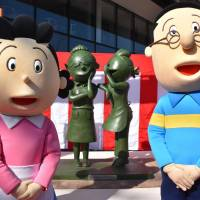 Characters pose in front of a statue of Sazae-san and the character's creator in Fukuoka.   KYODO