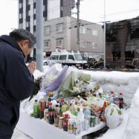 A man offers a prayer Wednesday in front of a residential facility for welfare recipients in Sapporo, where 11 people were killed in a fire that started on Jan. 31. | KYODO