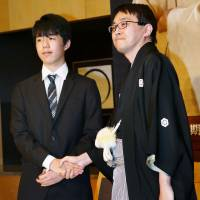 Yoshiharu Habu (right) and Sota Fujii shake hands at a news conference in Tokyo in January. | KYODO