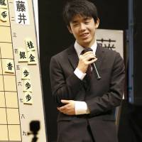 Sota Fujii faces reporters after beating 47-year-old shogi master Yoshiharu Habu for the first time in an official match Saturday in Tokyo's Chiyoda Ward. | KYODO