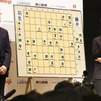 Sota Fujii (right) and shogi master Yoshiharu Habu review their match as Fujii beats Habu for the first time in an official tournament in Tokyo's Chiyoda Ward on Friday. | KYODO