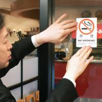 A restaurant employee puts up a 'No Smoking' sticker in Yokohama in April 2010. | KYODO