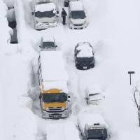 An aerial photo shows cars and trucks buried in snow and stranded on Route 8 in Sakai, Fukui Prefecture, on Wednesday. | KYODO