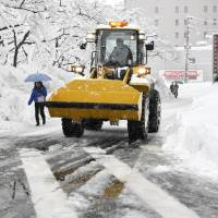 A man drives a snowplow on a frozen Fukui road on Tuesday. Last week heavy snow stranded 1,500 cars in the prefecture.   KYODO