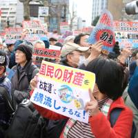 Protesters on Friday call for the resignation of Nobuhisa Sagawa, head of the National Tax Agency, in Tokyo's Kasumigaseki district. Sagawa was a senior Finance Ministry official when he told the Diet all records of the sweetheart land deal given to Moritomo Gakuen had been destroyed. A number of related documents turned up later, contradicting his testimony. | KYODO