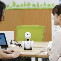 Nippon Telegraph and Telephone East staff members use the OriHime communications robot to talk with an employee working from home in September.   KYODO