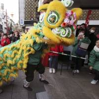 Lion dancers celebrate the Chinese Lunar New Year in Yokohama on Friday. Over the Lunar New Year holidays in February, the Japan Tourism Agency said many travelers from China chose to visit snowy areas such as Hokkaido, the Tohoku region and Niigata Prefecture. | AP