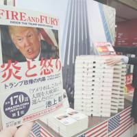 Copies of the Japanese translation of 'Fire and Fury: Inside the Trump White House,' are stacked in front of a photograph of Trump Tower at a bookstore in Chiyoda Ward, Tokyo, on Friday for its debut in Japan. | KYODO