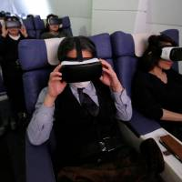Visitors wear virtual reality goggles as they 'travel' with First Airlines, a first-class airline experience facility in Tokyo, earlier this month. | REUTERS