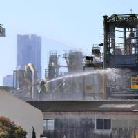 Firefighters hose down an chemical factory in Yokohama after a fire broke out there Monday. | KYODO