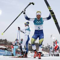 Charlotte Kalla, of Sweden, celebrates after winning the gold medal in the women's 7.5km /7.5km skiathlon cross-country skiing competition on Feb. 10. | AP