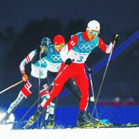 Akito Watabe (above, right) captured silver for Japan in the Nordic combined men's individual normal hill 10-km competition for the second straight games. | REUTERS